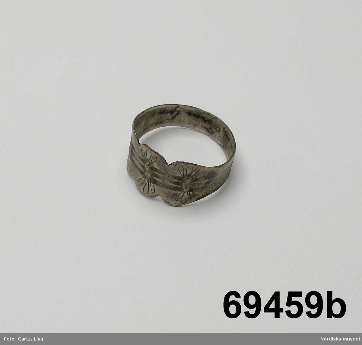 """Huvudliggaren: """"a-b  2 fingerringar fr. Jukkasjärvi sn, Torne lappmark. Af silfver. a. Stämpl: 'T 13 1/3 H H 79 [Båda H:na i skrivstil].' b. Stämpl: 'J O D. T5. h  o o [h:et i frakturstil och ovanför de två små ringarna vilar en tredje] Har tillhört en jukkasjärvilapp. G[åva] af handlande E. Wikman i Vittangi. Bil. Samzelius 162."""""""