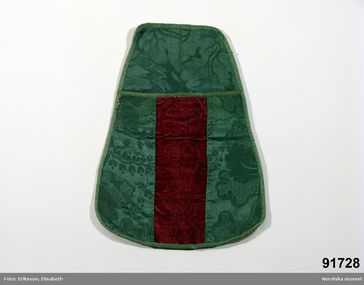 """Katalogkort: """"Kjortelsäck,  'Lomme' eller 'Snoppsäck'. Fästes vid ett band, som knöts kring lifvet, och hängde å bärarinnans högra sida, delvis under förklädet.""""  Avlång, något konisk form med avrundade hörn nedtill. Hopskarvad av flera små bitar. Bakstycket består av 2 bitar grön sidendamast sydda mot baksida av vit fin linnelärft, fickan sydd av 2 bitar grön sidendamast och i mitten en remsa mörkröd silkesammet med pressat mönster. Även fickan infodrad med vit linnelärft. Hela väskan kantad med gröna sidenband s.k. paduband av 1700-talstyp. Knytband saknas. /Berit Eldvik 2009-01-26"""