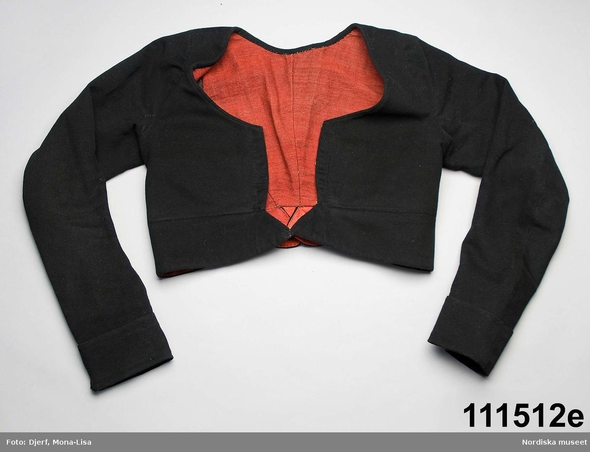 """Huvudliggaren: """"Kvinnodräkt, bestående av 2 liv, kjol, överdel, 1 tröja, förkläde, silkeshalskläde, 2 bindmössor med 1 stycke samt 1 par halvvantar.""""  Bilaga: Inget utöver huvudliggaren.  Katalogkort: d: Inga ytterligare uppgifter. a. Livstycke av halvsiden. . Foder av grov oblekt linnelärft. b. Livstycke av ljusblå sidendamast med blommönster i 1700-talsstil. c: Svart kjol av halvylle.   D:1.Överdel av tuskaftat vitt halvlinnetyg.  e.Kvinnotröja med skört, av svart kläde,"""