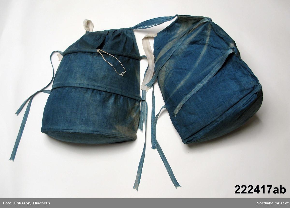 """Ett par pocher a-b.  Av indigofärgad, mellanblå linnelärft, 2 """"påsar"""" utspända med hjälp av 3 rader valben lindade med oblekt linne. Insidan som vilar mot kroppen är rak, utsidan utspänd med en halvcirkelformad bottenplatta. Hålrummet som bildas i påsen kunde fungera som stora fickor med en sprundöppning upptill. Pocherna hänger ihop med ett ljusblått sidentaftband, dubbla knytband av sidenband s.k. paduband att knyta fast pocherna med. Satt en över var höft för att hålla ut kjolvidden i sidled. /Berit Eldvik 2009-11-30"""