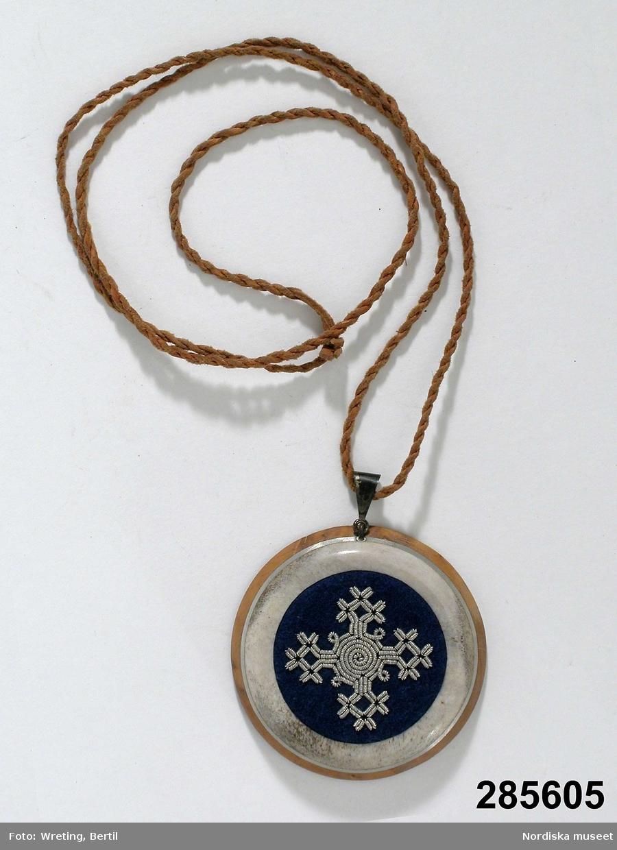 """Huvudliggaren: """"Hängsmycke, runt; bottenplatta av rödbrunt trä, grått horn infällt med en rand av tenn mellan; på framsidan likarmat kors i tenntrådsbroderi på blått kläde; sign. 'EM-NN'; halsrem av tvinnat läder. Diam 5,5 cm, H ca 1 cm, L rem ca 70 cm. Tillv. av Ella-Margit och Nic. Nutti. I[nköpt] 26/7 1972 [från] Ella-Margit Nutti, Gällivare [...]. [Brukningsort:] Lappland Gällivare."""""""