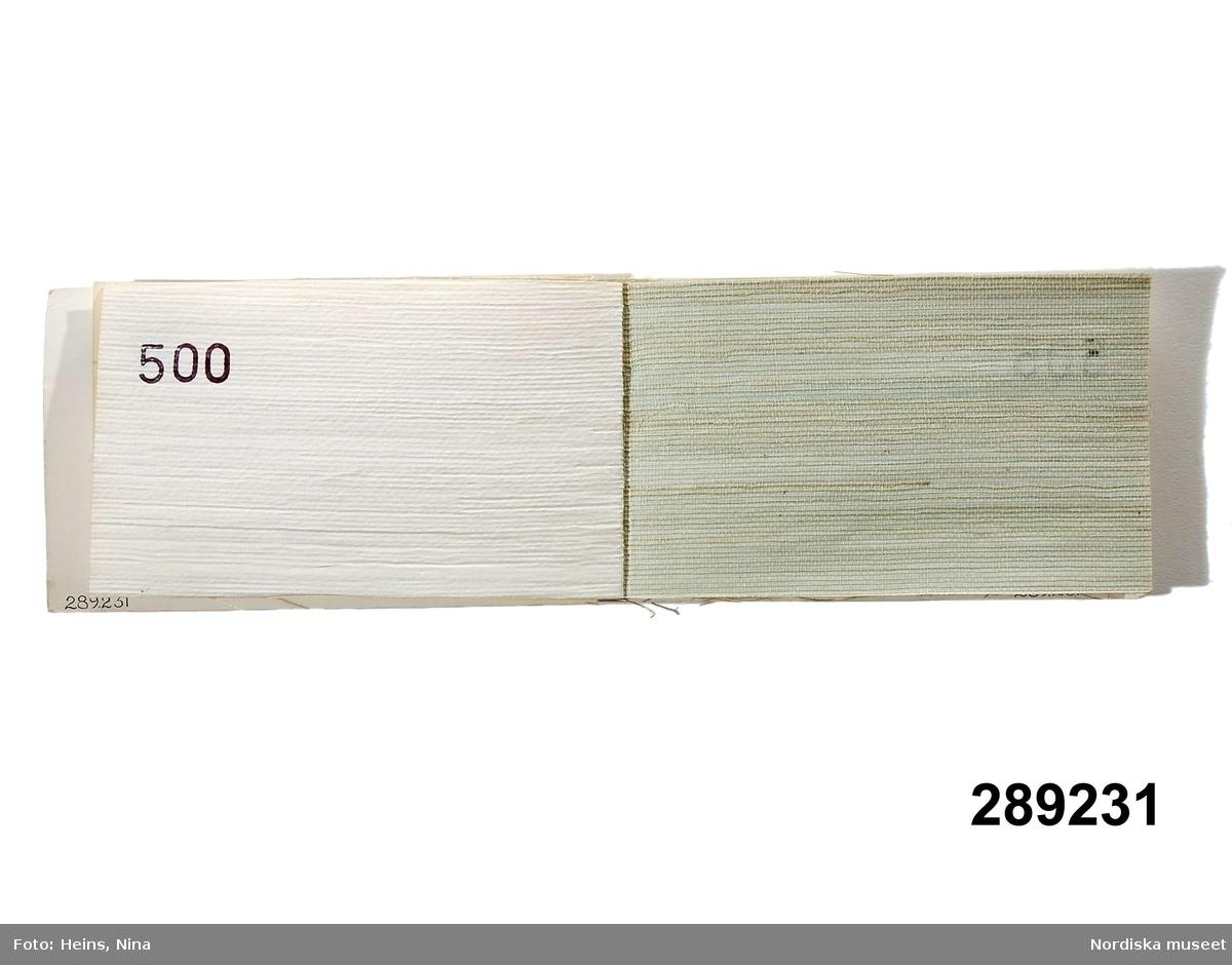 """Huvudliggaren: """"Tapetprover, häfte, papperspärmar; 23 st tapetprover av hamp- och linneväv på pappersbaksida. Mått häfte 10, 2 x 18 cm.""""  Katalogkort: Ingen ytterligare information utöver huvudliggaren.  Limmat omslag i plastat papper med text """" Hampa Lin  AB ASIATA LTD STOCKHOLM NO TELEFON 08/600530, 260561, 260017."""" På baksidans pärm finns en reklamtext samt kort information om hampa och lin. Första bladet med prislista för januari 1965. Samtliga tapetprover med produktnummer stämplat på baksidan. Tapeternas färger är i olika nyanser vit, beige, rosabrun, grön och gul. /Cecilia Wallquist 2006-11-24."""