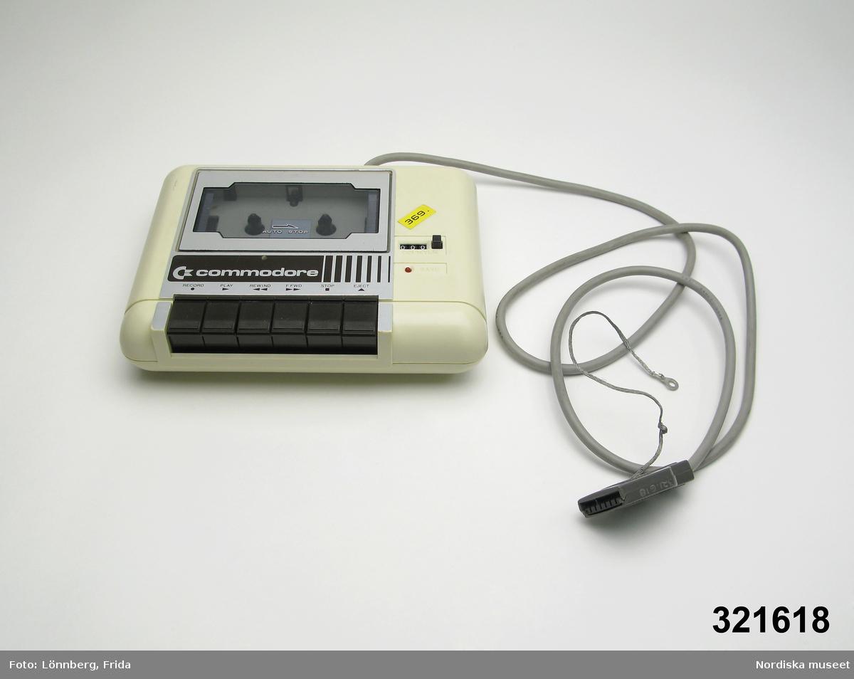 """Inventering Sesam 1996-1999: L 19,5 cm B 15,5 cm Kassettbandspelare i ljusgrå plast, avrundade hörn och kanter, ovantill lucka för kassettband och sex svarta knappar (ex """"RECORD / PLAY / REWIND""""). Räkneverk. Gul etikett """"369"""". Undertill flera silverfärgade etiketter ex """"COMMODORE / MADE IN TAIWAN/ C2N CASSETTE / SERIAL NO. 3440085"""". Grå elsladd (jordad) med stickkontakt (att koppla till datorn). På kontakten grå vajer (för jordning). Axel Brundin (född 1977) fick datorn i julklapp. Den var köpt från pojkarna Norman (födda 1971) som tidigare använt den. Dataspel och tillhörande föremål; Tangentbord ivn.nr 321.617 kasettbandspelare inv.nr 321.618, transformator inv.nr 321.619, Kasettväska med kasettband med olika dataspel inv.nr 321.620:1-24, tre joy sticks inv.nr 321.621 och 321.622, skokartong inv.nr 321.623 (i vilken kasettband förvarades)  och Kasettband med spel 321.624-321.639 Instruktionsböcker, band- och kundförteckning finns på arkivet. Bilaga Elisabet Brundin 1995 Leif Wallin 1998"""
