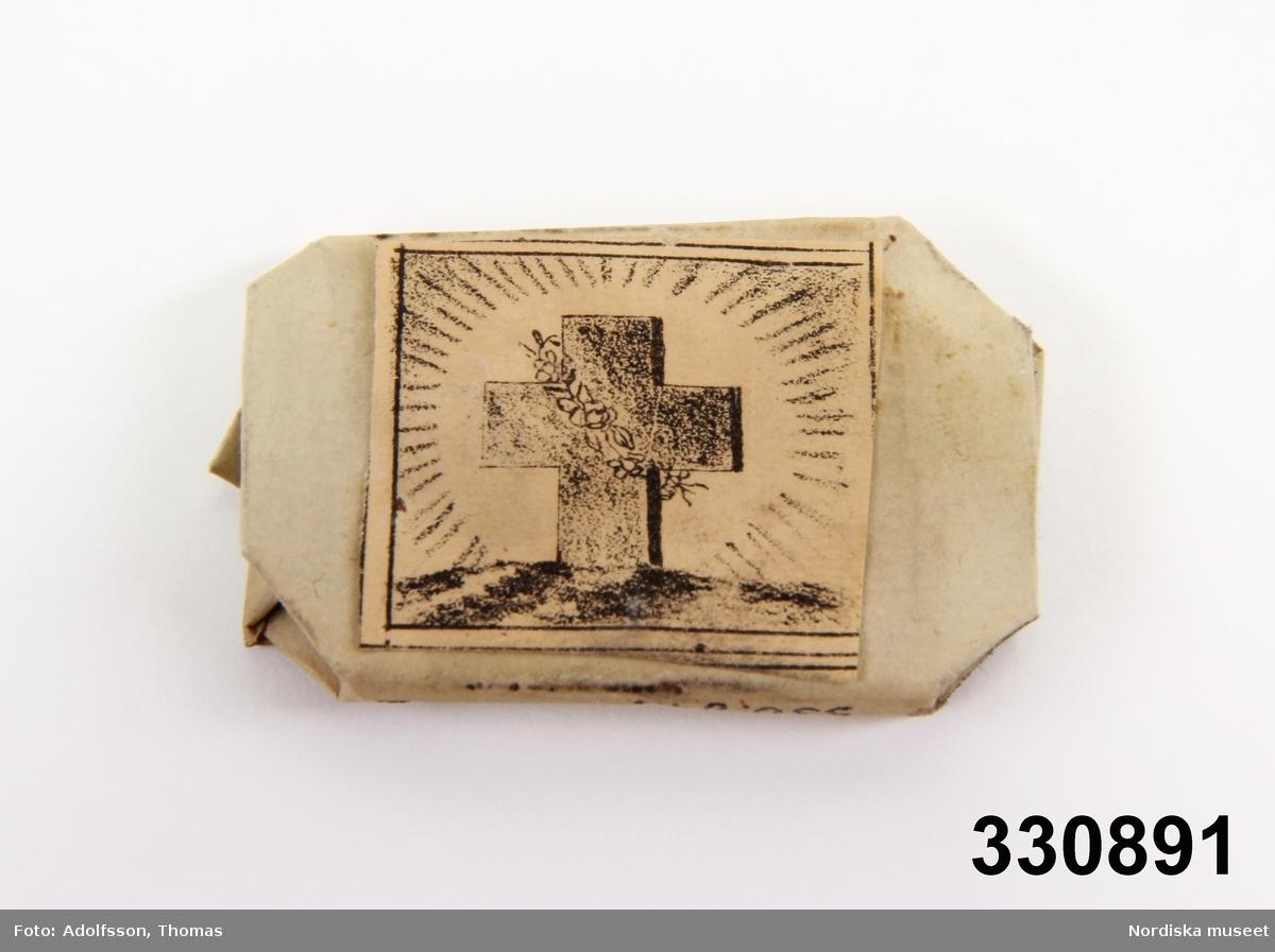 Papperskaramell, snedvikta hörn, litografi: kors i strålkrans, rosenslinga runt.   Heidi Henriksson 2006-01-24