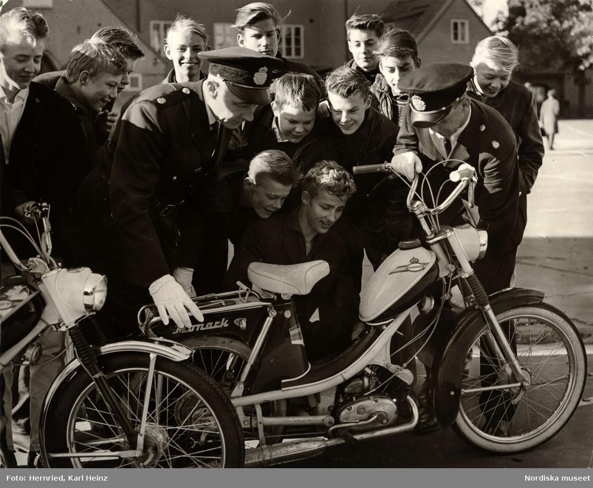 Polis i skola. Två polismän och en grupp pojkar undersöker en moped av märket Monark (monarpeden).