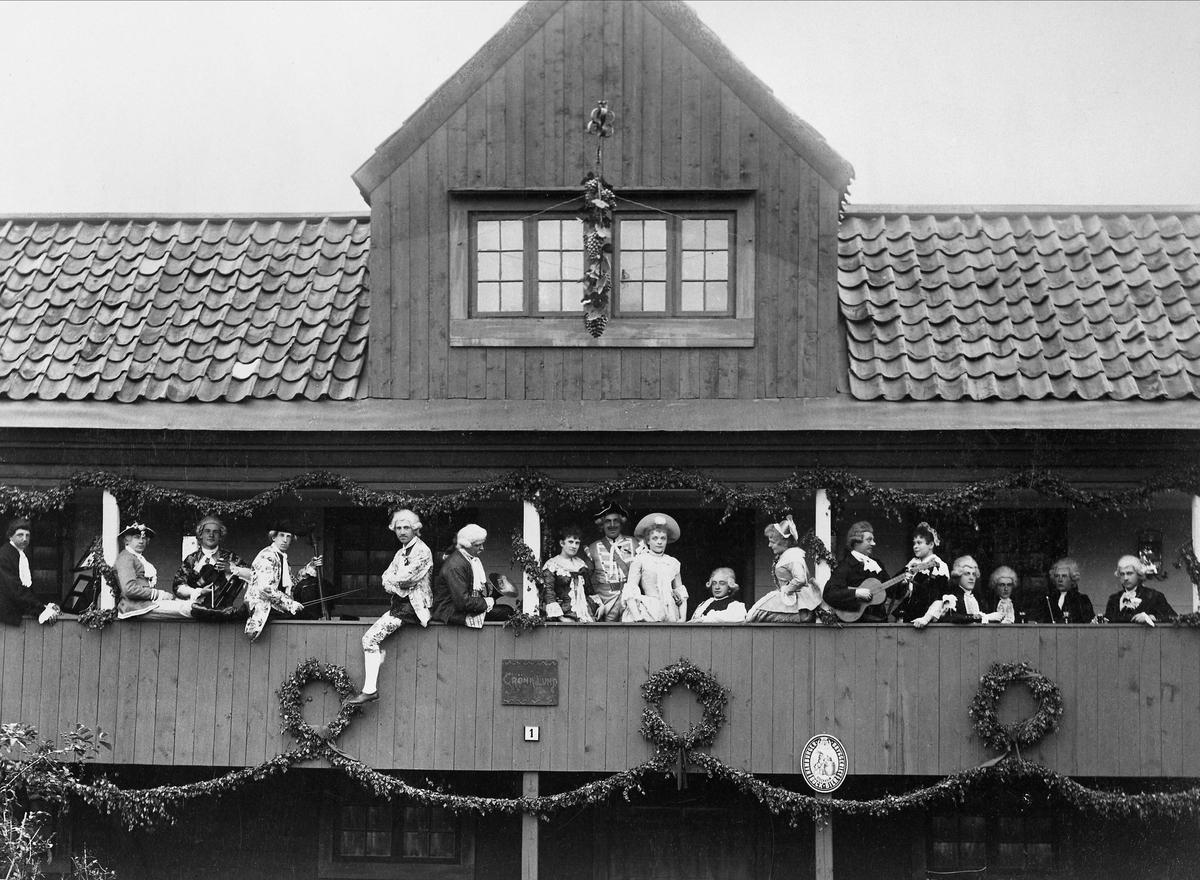 Skansens vårfest 1894. Ett sällskap män och kvinnor iförda 1700-talsdräkt på Gröna Lunds loft. Vissa av männen med instrument.