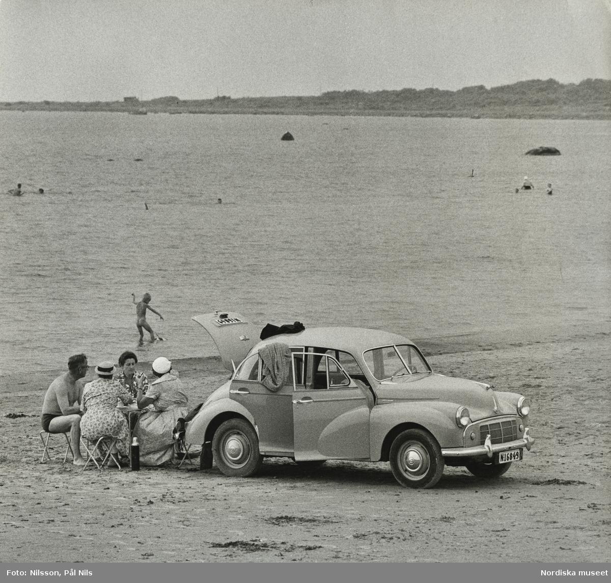 En bil, Morris Minor, parkerad på badstrand vid Frösakull, Halland. Tre kvinnor och en man sitter vid picknickbord, badande pojke i bakgrunden.