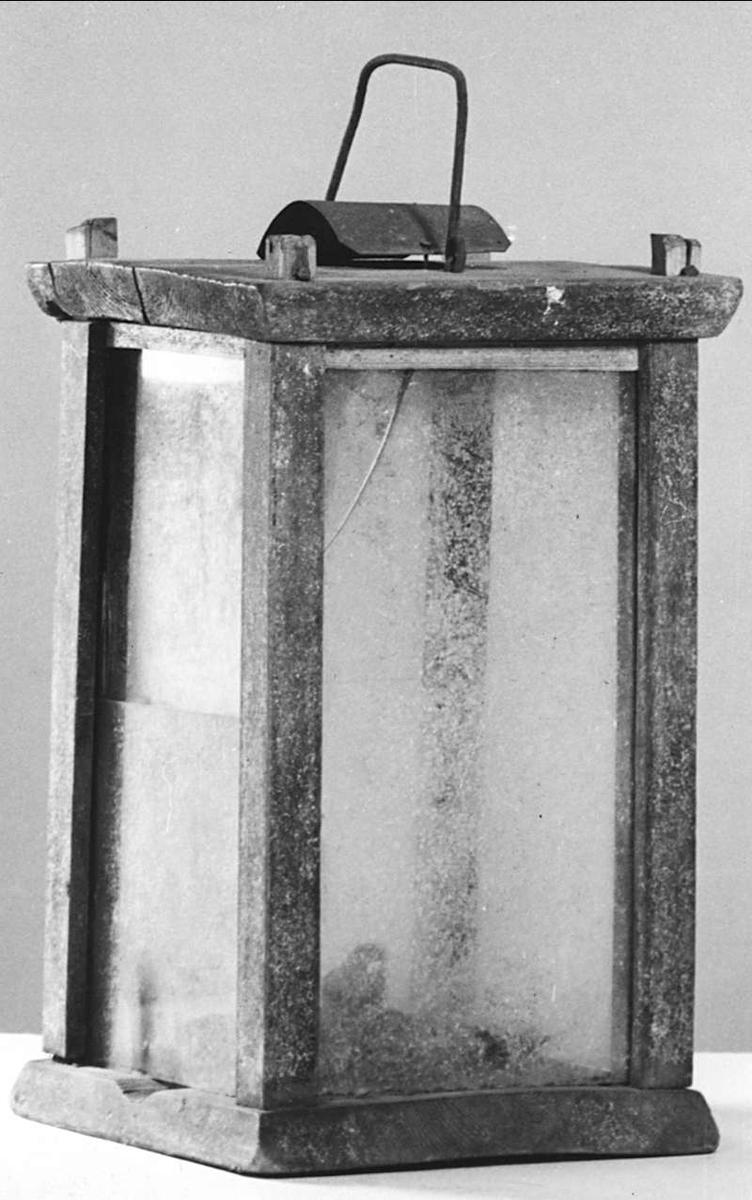 Lykta av trä och glas. ljushållare av mässing, handtag av järn.