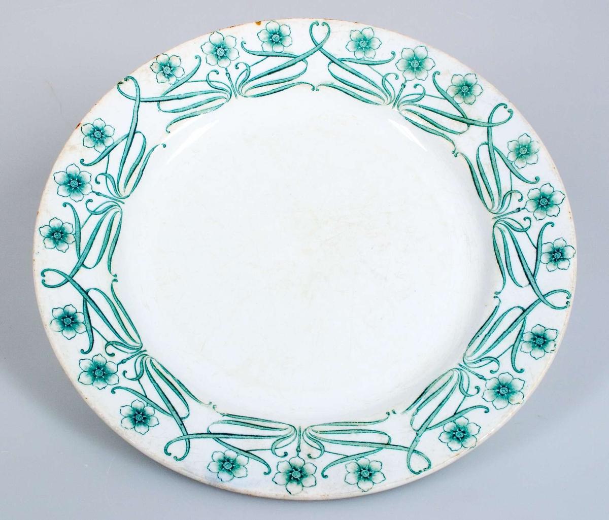 Vitglaserad med tryckt grön dekor. Grön tryckt stämpel: CHIC Gustafsberg. Instämplat i massan: Gustafsberg OPAK O2.