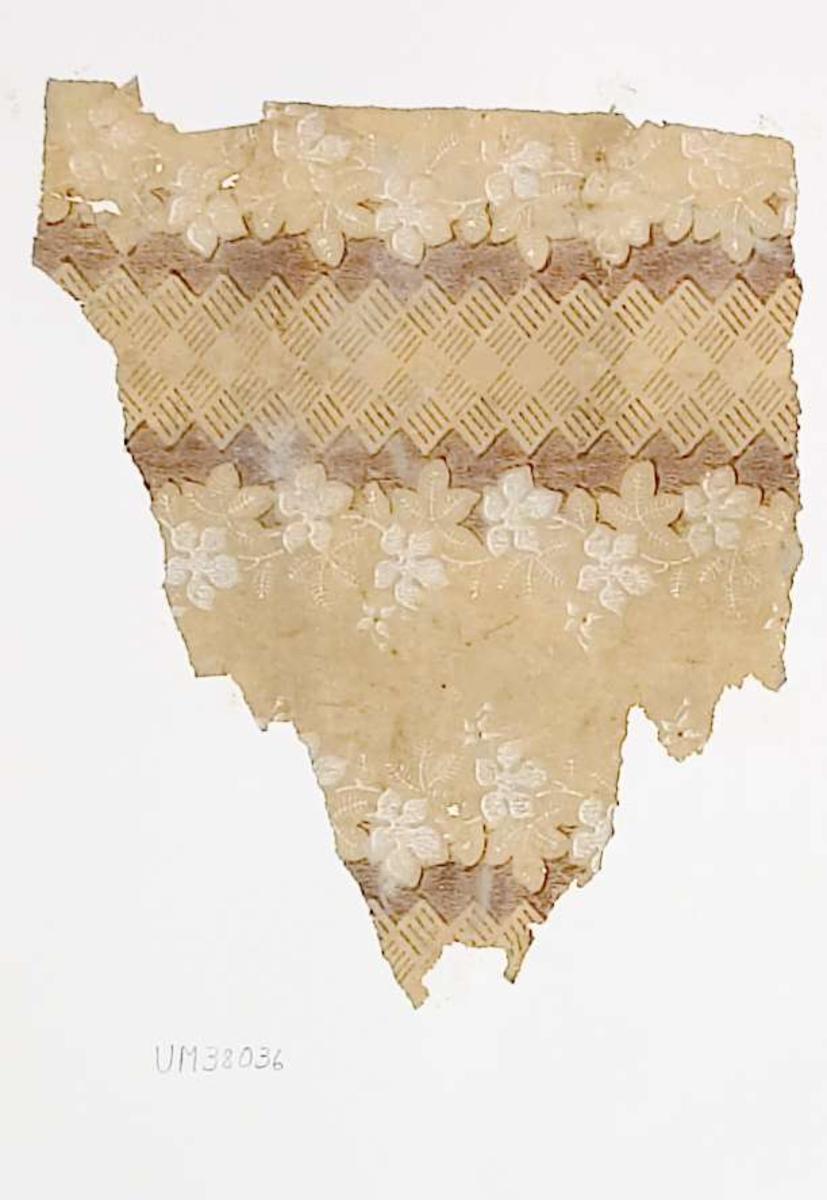 Tapetprov med tryckt mönster, gult, brunt och vitt. Handskriven text på baksidan av kartongen: 242 Kv. Munken, Enköping Munksundsg. 3 ö.b. Understa tapetlager på stänkmålningen 1.