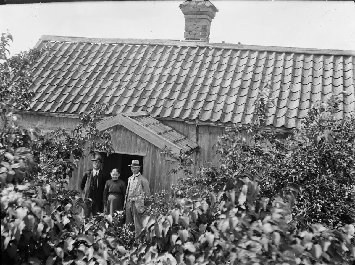 Två män och en kvinna framför bostadshus, Uppland