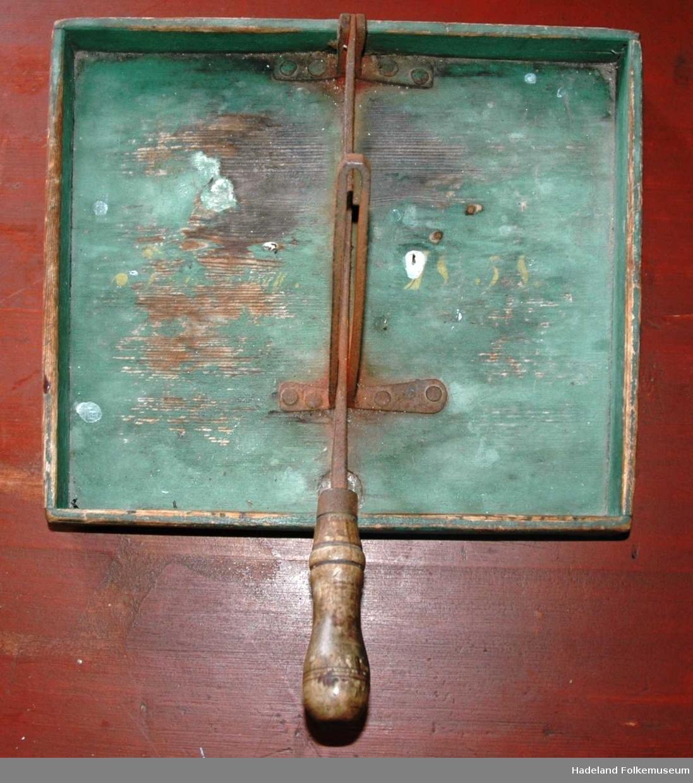 Grønmalt kasse med påmontert kniv midt på.