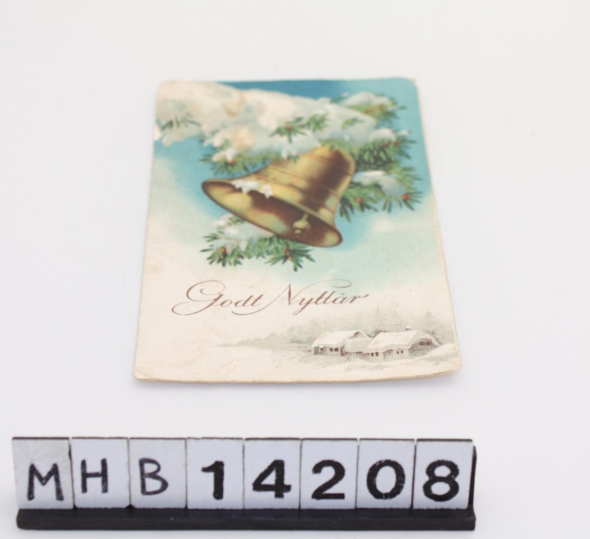 Rektangulært postkort med julehilsen. På en side er håndskrift og på den andre siden er motiv. Motivet består av et par snøkledde hus foran granskog nede i høyre hjørne. Midt på er en bjelle som henger på en snøkledd grein.