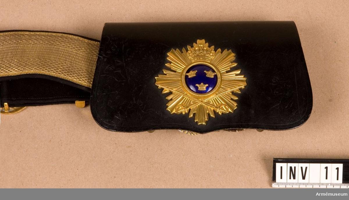 Av en plåtask överdragen med lackerat svart läder. Inredd för 12 patroner. På utsidan förgylld vapenplåt med blåemaljerad glob. Nertill tappar för att fästas i kartuschremmen. Har tillhört Gustav VI Adolf (1882-1973).