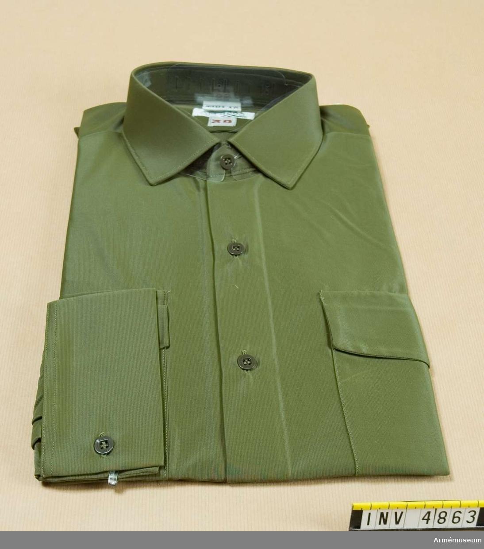 Skjorta m/1968, Svea livgarde. Storlek: 39.Skjorta m/1968, grön. Av grön nylontyg, har fast krage, fasta axelklaffar med hylsor samt två bröstfickor med ficklock och  knapp. Källa: UNIA 1977 6:13-15.