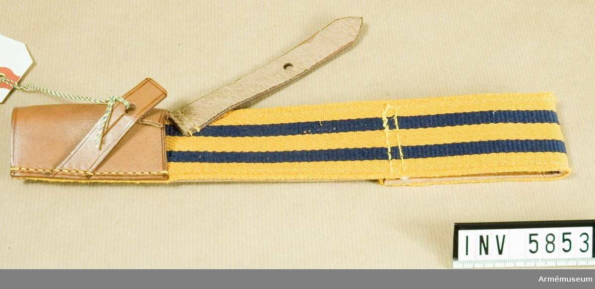 Samhörande gåva 5828-5899 + 6000-6099 + 6200-6205. Hylsa m/1931 till bajonettbalja för alla truppslag.Gott skick X2. Längd 270 mm, bredd 45 mm. Färg gul C, blå M.Fastställt genom go 21 november 1931 nr 2506. Hylsan är av kypertvävt redgarn i gult med två mörblå ripsvävda ränder,  vardera 7 mm breda. Bandet är fodrat med ljust läder och upptill vikt dubbelt till en tunnel, genom vilken man skall dra  skärpet m/1910-1931. Hylsan för bajonetten är av ljust läder  och sitter nedtill på rätsidan. Två snedställda läderremmar skall knäppas mot bajonetten.