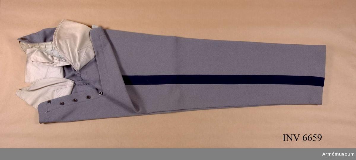 """Ylle. Storlek 100. Grå långbyxor med mblå klädeslist Över yttersömmen och börjar i framfickan, 40 mm bred. Jylfknäppta och försedda med knappar för hängslen. Två bakfickor. Långbyxor, lämpligen med hällor försedda, bäras alltid vid paradtillfällen utom vid tjänstgöring till häst. Under Övningar  i terräng bör långbyxor vara dubbelt uppvikta med en bredd å  uppvikningen av omkring två fingerbredder. TjR 17:19. Källa: Landstormens publikationer nr 1 """"Landstormsofficerens klädsel"""", Landstormssällskapet, Stockholm 1930, Brolins boktryckeri."""