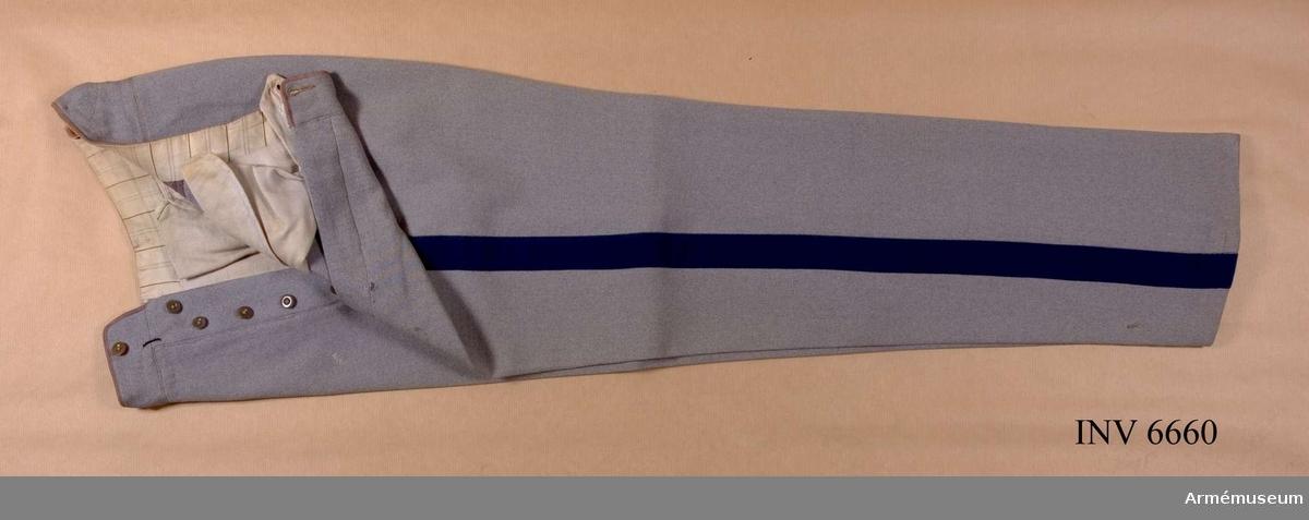 """Ylle. Storlek 100. Grå långbyxor med mblå klädeslist Över yttersömmen  och börjar i framfickan, 40 mm bred. Jylfknäppta och försedda  med knappar för hängslen. Två bakfickor. Långbyxor, lämpligen med hällor försedda, bäras alltid vid  paradtillfällen utom vid tjänstgöring till häst. Under Övningar  i terräng bör långbyxor vara dubbelt uppvikta med en bredd å  uppvikningen av omkring två fingerbredder. TjR 17:19. Källa: Landstormens publikationer nr 1 """"Landstormsofficerens klädsel"""", Landstormssällskapet, Stockholm 1950, Brolins  boktryckeri."""