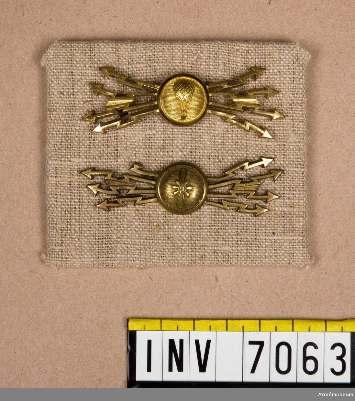 På platta två kompanimärken m/1912, flyg- och ballongkompani, Fälttelegrafkåren. Plattans storlek 80 x 70 mm.  Kompanimärke för Ballongkompaniet och för Flygkompaniet. Bärs i mössan.