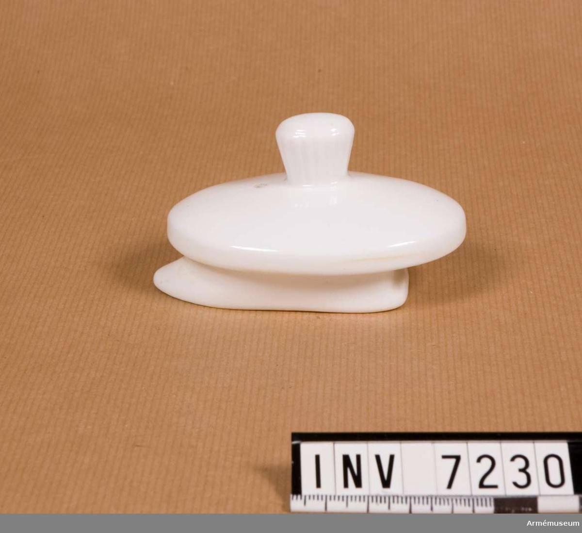 Samhörande nr är 7216-26, 7228-30 (7229-30 kanna, lock). Ett helvitt lock med ett refflat handtag, lufthål och med utformning i botten för att ej glida ur kannan vid upphällning.  Gott skick.