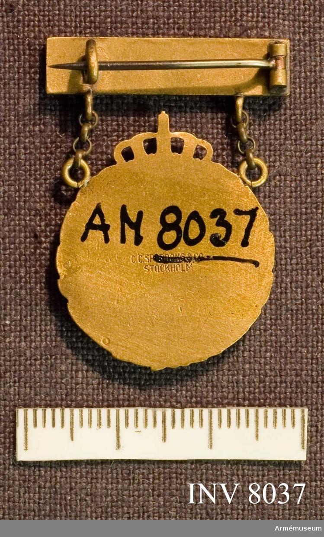 Samhörande gåva 8020-. Idrottsmärke, ungdom, årtalsmärke. Märket hänger i ett spänne på vars platta två blåemaljerade stjärnor sitter. I det runda märkets mitt är ett fyrdelat emaljerat märke, två gula och två blå delar. Tillverkare Sporrong. Höjd 2 mm (tjockleken). Längd 25 mm (plattan). Färg brons och blå och gul emalj. Idrottmärket är instiftat av Svenska gymnastik- och idrottsföreningars riksförbund. Se Landsofficerssällskapets publikationer nr 1, 1930.