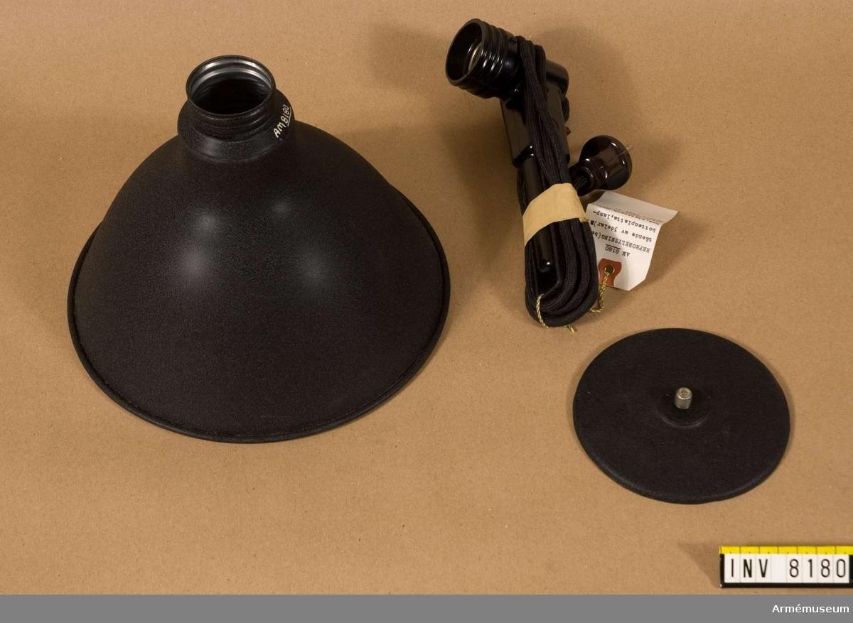 Reprobelysning. Varje nummer består av tre delar: reflektor, stativ (handtag) och fot (tyngd). Färgen är svart och silver. Samhörande nr är AM.008151 - AM.008199.