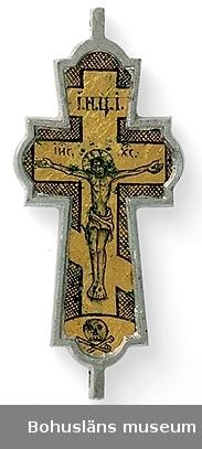 """Guldfoliebelagda glas (på båda sidorna) där olika religiösa symboler ristats; på ena sidan Kristus uppspikad på ett ryskt kors, en dödskalle; på andra sidan en kalk, en duva, Moses stentavlor, en bibel samt rysk text. Glasen insatta i en gjuten och bearbetad korsform av tenn. Hål för montering gjorda i över- och nederdelen.  Uppgifter på gammal etikett som varit fastknuten vid föremålet: Kors av metall o glas från Solowetsk kloster n. Arkangel. Hemfördt och skänkt av Adjunkt Theodor Björnberg i Uddevalla. """"Eac27b"""" skrivet med rött bläck på etikettens övre del.  Ur handskrivna katalogen 1957-1958: Kors av Glas och metall Ryssl. Mått: 8,7 x 3,8 x 0,8 cm; på båda sidorna förgyllda fält, d. ena m. Kristus, d. andra symbol. bilder jämte --ska Helt."""