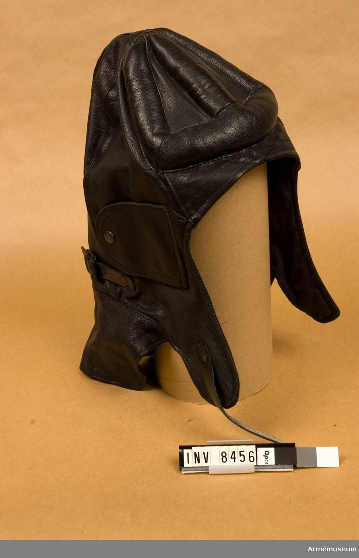 FMV:Bekläd skr 183-06-01 Int A 617:331/83. Av svart skinn fodrad med svart bomullstyg. Vadderat skydd för hjässan, öronklaffar och spännret under hakan och halsen. Fodret är kronstämplat och bokstäverna L L M.