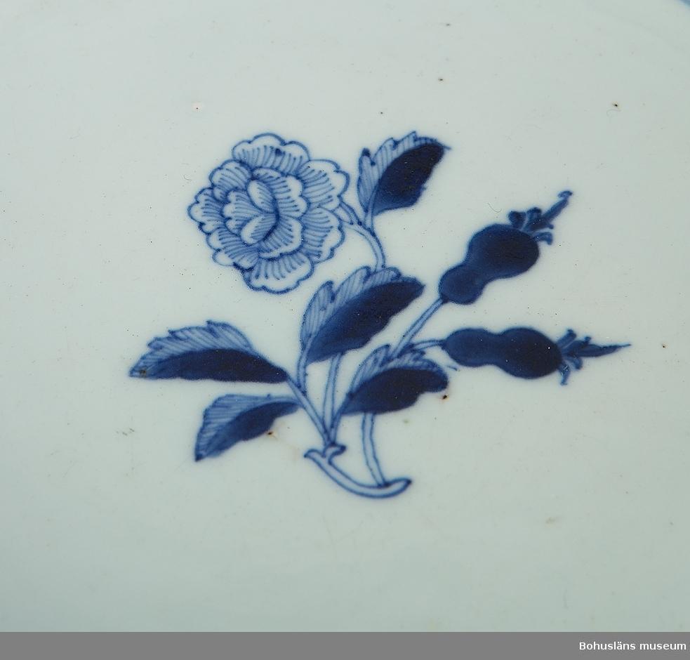 Ur handskrivna katalogen 1957-1958: (Ostindisk) skål, blå Mynningsdiamet. c:a 22,5 cm H. c:a 5 cm. Vit med blå bård och blått blommotiv. Skålen hel. [Den har en omfattande lagning på ett ställe på kanten. /Noterat mars 2014]  Troligen från åren runt sekelskiftet 1800-talet. Exportporslin, dvs gjort för den europeiska marknaden och transporterat hit med de ostindiska kompanierna.