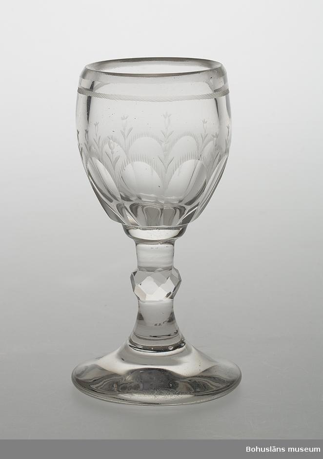 Sammanhör med UM004728  Ur handskrivna katalogen 1957-1958: Varbergsglas 11,5 cm. Mynningsdiamet.: 5,2 cm. Vitt tjockt glas m. etsat mönster. Slipad vulst å foten. Rund fot. Föremålet helt.