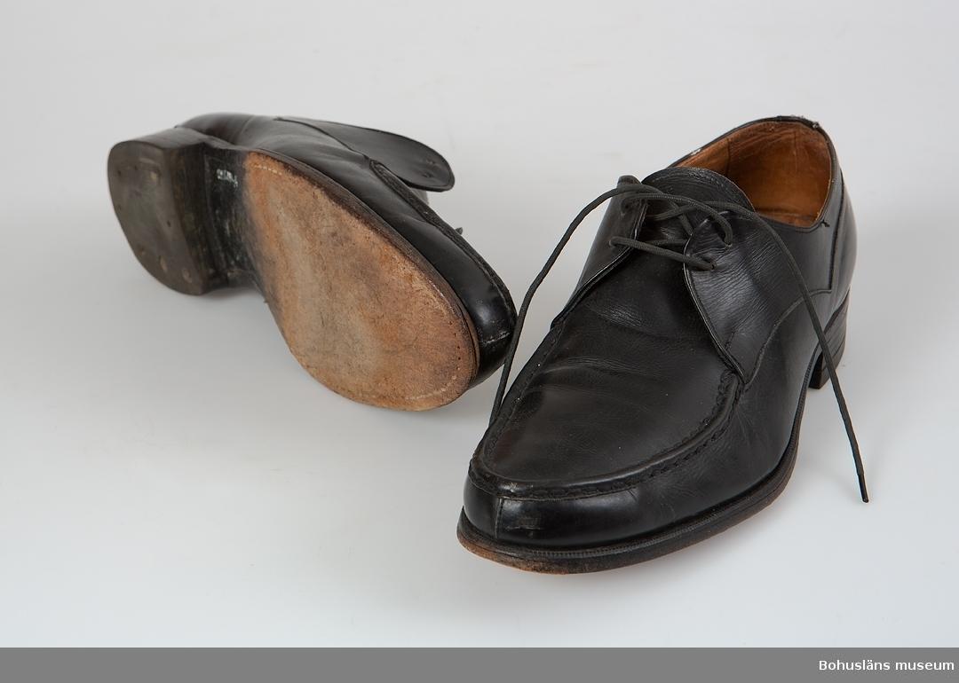 Ett par svarta skinn-/läderskor. Sula av läder, klack av gummi. Skosnöre saknas på högerskon. Troligen 1950-talet.