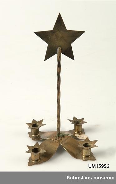 Fot av korsställda bladliknande mässingdelar med fyra ljushållare. I mitten vriden stång med femuddig stjärna. Avsedd för julgransljus.  Se UM015810