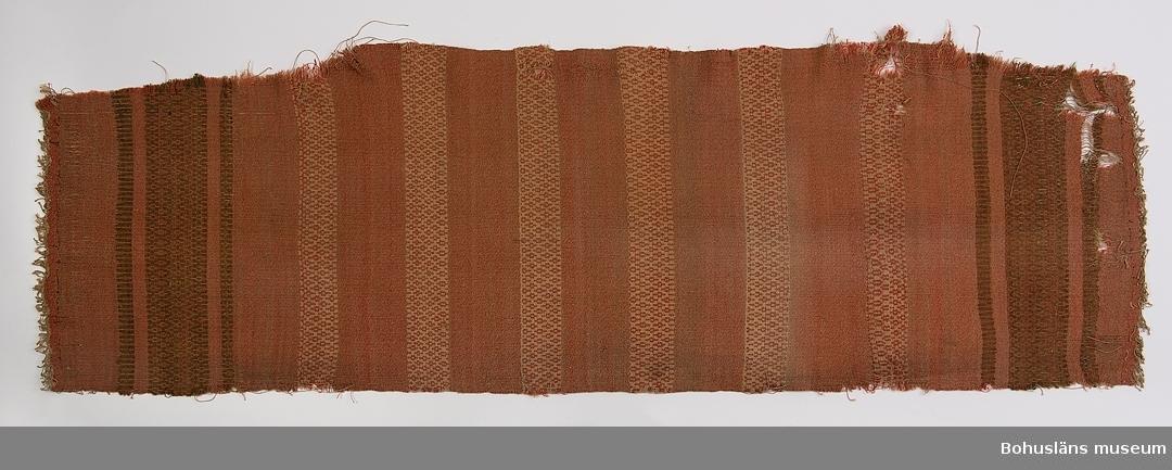 Vävnad i bunden rosengång, solvad på 4 skaft, glest vävd. Med omväxlande partier med tuskaft och bårder med små romber. Tuskaften är melerad i ljusbrunt och gulrött. Mönsterbårderna närmast kortsidorna är bruna och gulröda, de i mitten beige och gulröda. Inslagen är gjorda med ullgarn. Varpen är av beige bomullsmattvarp. Varptrådarna är sammanknutna vid kanterna, en del dock ej knutna. Hörnorna vid ena långsidan är snedklippta. Några centimeter av vävnaden ytterst längs andra lånsidan har mörkare färg. Slitmärken finns mest längs ena sidan. Dessa saker tyder på att vävnaden varit använd som möbelklädsel på en soffa. Med dateringen till 1900 ca menas inte att vävnaden med säkerhet är gjord 1890-1910 utan att den kan vara från slutet av 1800-talet men lika troligt från första delen av 1900-talet. Mycket sliten. Trasig på flera ställen längs långsidorna. Stora bristningar vid ena kortsidan och mindre vid andra. Slitmärken mest på ena  halvan.  För ytterligare uppgifter om givaren se UM016001