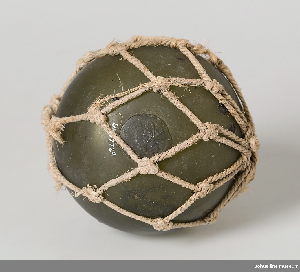 Grön glaskula. I proppen där glasblåsarpunteln suttit intryckt är det en treklöver i relief. Inknuten i tågvirke. Tågvirket är söndrigt.