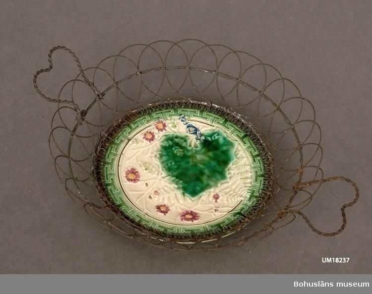 Assiett i keramik (majolika) på vilken satts ett kantgaller av järntråd. Jämför UM18238.  Järnet rostat.