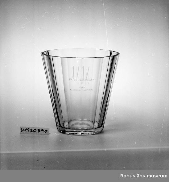 """Nedåt konande form, bottendiameter 15 cm; utsidan 12-kantigt slipad. Klarglas. På ena sidan graverat: """"N.D."""", på andra: """"På 50-årsdagen /19 29/1 36 från Kampenhofs tjänstemän"""". I botten graverad signatur: """"Orrefors 1936"""". Formgivning troligen Simon Gate. Nils Dreijer, disponent för Kampenhofs bomullsspinneri, Uddevalla 1928-1953."""