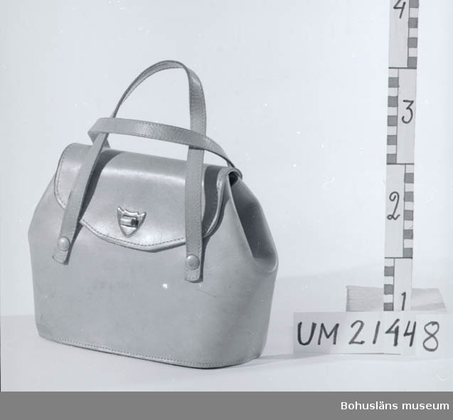 Två läderremmar som handtag och fastsatta med fyra metallnitar.  Väskan har ett vridbart lås. Foder av galonliknande tyg. Använts av kvinna.