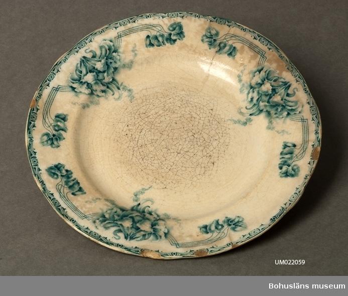 """Tallriken är vitglaserad med blå blomstermotiv runt brämet.  Den är naggad i kanten, krackelerad och missfärgad under glasyren.  Att servisdelar från 1800-talets slut och 1900-talets början ofta fått ett missfärgat och skadat utseende beror ofta på att dessa ställdes in i ugnen eller värmdes upp med hett vatten (potatisvatten) innan man serverade på dem. Glasyren på viss typ av gods tålde inte den typen av upphettning utan mikrosprickor uppkom som fett och mjölkprodukter o.d. kunde tränga in genom. Även ofräscht diskvatten kunde säkert göra sitt till.  """"Original"""" i modellnamnet tyder på att det var ett mönster som fabriken själv tagit fram. Mönsterschablonen var inte köpt från exempelvis England som annars var vanligt vid fabriken.  Litteratur: Artikel i Antik & Auktion nr 1 1983. Göteborgs porslinsfabrik - den okända fabriken där Grön Anna föddes. Skriven av Jane Fredlund."""