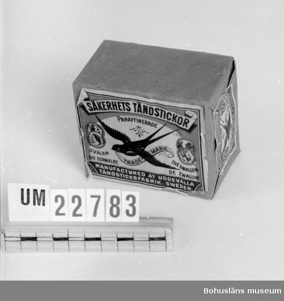 """Föremålet visas i basutställningen Uddevalla genom tiderna, Bohusläns museum, Uddevalla.  394 Landskap BOHUSLÄN  Grått papper med etiketter och fabriksmärke. Text: """"Säkerhets Tändstickor paraffinerade. Svalan trade mark"""" samt en svala och fyra medaljonger. Vit etikett på baksidan med text:""""Uddevalla Tändsticksfabrik. Datum d.27/3 1926. Sats, Gul Te8. Plån. G14. Paraffinering. Impregnering. Klister. Format 52 Etikett. Svalan. Splint. Order Nr: """". A.B.Bohus-Postens Boktryckeri Uddevalla.  Neg.UMFF 139:2  November 2006 - uppgift från Christer Langborg, Vårby, född 1945; han har varit innehavare av Langborgs cigarraffär vid Kungstorget, Uddevalla: CL:s farfar Sven Langborg hade arbetat vid Uddevalla tändsticksfabrik och bl a gjort förlagan till etiketten Svalan. Ytterligare en etikett hade han gjort men det mindes inte CL vilken det var. Christers far hette också Sven Langborg (1909-1986) vilket kan bidra till förväxlingar.   För mer informaton om Uddevalla Tändsticksfabrik, se UM16637."""