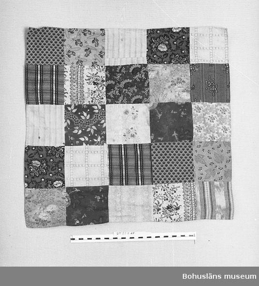 Docktäcke av 25 fyrsidiga bomullslappar. Tryckta mönster. Bitar av antingen ägarnas kläder eller av rester från sömnaden därav. Ett par mindre hål samt några fläckar.  Personuppgifter se UM023863