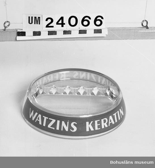 """594 Landskap BOHUSLÄN  Ofärgad glas. På kanten pålagd blå färg med vit text: """"Watzins Keratin"""". Ingick i frisérsalongens inredning. Föremål från Brorssons Damfrisering i Kungshamn, se UM023941."""