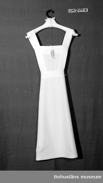 """106 OCM 743, 292 594 Landskap BOHUSLÄN  Vitt. """"Kjol"""" med lapp för bröstet. Helt öppen baktill. En utanpåficka på kjolen.  På lappen sitter två axelband, ca 6 cm breda, vilka knäpps fast med vita knappar i kjolen bak på ryggen.  På insidan vid nederkanten finnst två stycken vita märklappar, text: """"42"""", """"STJ"""". """"95."""" broderat med rött. Hör ihop med UM24529 och UM24530."""