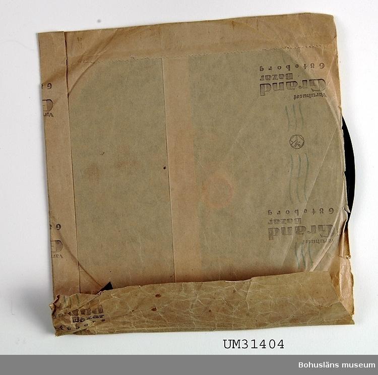 Grammofonskiva, stenkaka i papperfodral märkt Varuhuset Grand Bazar, Göteborg. Ena sidan: Folkvisa. Merikanto. Operasångaren Martin Öman.  Andra sidan: Serenad. Widéen. Operasångaren Martin Öman.   Skivmärke: Polyphon  Grammofonskivan som ingår i skivsamling som spelats i en sommarstuga i Sundsandvik, byggd 1939. Skivorna spelades på en svart resegrammofon, se motsvarande modell UM026268. För ytterligare upplysningar om förvärvet, se UM031385.