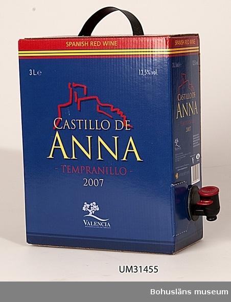 Tom förpackning för lådvin, boxvin eller bag-in-box-vin för tre liter vitt vin av märket  Castillo de Anna Blå papperslåda innehållande tom plastpåse med tappkran av plast. Bärhandtag av svart  plast. Grafisk röd bild på långsidorna, bl.a.  med texten: SPANISH  RED WINE CASTILLO DE ANNA TEMPRANILLO 2007 VALENCIA DENOMINACION DE ORIGEN 13 % VOL 3 LITRES På kartongens undersida beskrivs i text och bild hur lådan öppnas och kranen tas fram.