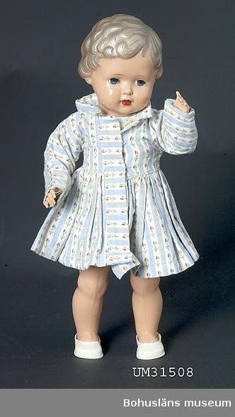 """Kort kappa i blå-och vitrandigt bomullstyg med broderade rosenknoppar. Lång ärm, ståkrage och rynkad kjol. Knäpps med tryckknappar. Kappan är"""" reskläder"""" till dockan Kerstin, tillverkade av givarens mamma, se UM31508. Se fotografi på ägaren med dockan Kerstin, UMFA55058:0023.  Föremålet har använts av familjen Abrahamson i deras sommarstuga i Sundsandvik, byggd 1939. För ytterligare upplysningar om förvärvet, se UM031385."""