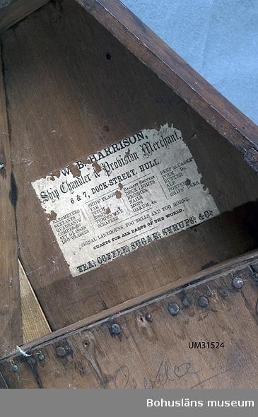"""Oktant i trekantigt schatull av mahogny med sinkade fogar. Oktant med ram av ebenholts, mätskala av elfenben. På oktantens trädel inristade initialerna HL [?] Schatull med lock med upphöjning för instrumentet som stängs med två haspar och innanförliggande mässingslås, nyckelhål där nyckehålsskylt och nyckel saknas. Lådan är illa medfaren med sprickor och materialbortfall, ett trasigt gångjärn. Locket undertill lagat med påspikade tunna mässingsbleck.  På lockets insida fastklistrad pappersetikett med tryckt text i olika stilsorter: W. B. HARRISON Ship Chandler Provision Merchant 6 & 7, DOCK- STREET, HULL. BAROMETERS SEXTANTS QUADRANTS COMPASSES SPY GLASSES LOG GLASSES SHIPS' FLAGS TAR PITCH ROSIN TURPENTINE SCRAPERS BALLAST SHOVELS DECK LIGHTS BRUSCHES NAILS MOPS OAKUM &c. BEEF in CASKS PORK Do. BUTTER ALE PORTER SHIPS' BEER SIGNAL LANTHORNS, FOG BELLS AND FOG HORNS CHARTS FOR ALL PARTS OF THE WORLD. TEA, COFFE, SUGAR, SYRUP & C På lockets insida antecknat med blyerts """"Gerda"""".    Följande uppgifter om  W. B. HARRISON Ship Chandler Provision Merchant  Hilmer Ferdinand Edman, Flatön var kompassmakare, hemmansägare och sjökapten.    Det finns tre generationer kompassmakare på Flatön: 1. Hans Johan Edman, Fiskebäckskil. 2. Dennes son, Hilmer Ferdinand Edman, Flatön (1848 - 1938). 3. Dennes son, Folke Edman, Ängön (1909 - 1993) Till gåvan hör också en kompass.  Briggen Gerda byggdes 1868 på Olof August Bodins varv i Gävle. Hon såldes året därpå till ett rederi i Mollösund. Fartyget hade en besättning på nio man, alla från Orust utom en som var från Tjörn. Den första skepparen hette Johan Thorbjörnsson. Under 60 år gick Gerda i fraktfart med stångjärn, trä, lera, kalk och kol till hamnar i Sverige, Medelhavet och England. Fartyget bytte ägare flera gånger, bl. a. med Hilmer Ferdinand Edman från Flatön som ägare. Gerda blev till slut den äldsta briggen i Europas handelsflotta. Briggen såldes till Gävle stad 1930 av sin siste ägare där hon blev liggande som museifartyg. Hon"""