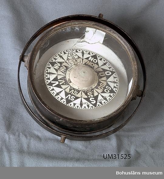 Rund skeppskompass i svartmålad cylindrisk kompasskål av metall , kardanskt upphängd i ett kraftig plattjärn. Kompassväggen är invändigt svartmålad med dubbla vita styrstreck i de fyra väderstrecken. Kompassen har en graderad handmålad kompasskiva i aluminium med kompassros i svart och vitt med väderstreck angivande NO, O SO, S, SV, V och NV. Norr är angivet som en utsirad pil. På skivans innersta cirkel närmast oläslig märkning, möjligen CARL ENG… I yttre cirkel signerad H F E 346.  Gradskivan är fuktskadad. En bit av det kraftiga glaset på undersidan har ramlat ur och ligger kvar invändigt.   Hilmer Ferdinand Edman, Flatön, var kompassmakare, hemmansägare och sjökapten.   Det finns tre generationer kompassmakare på Flatön: 1. Hans Johan Edman, Fiskebäckskil. 2. Dennes son, Hilmer Ferdinand Edman, Flatön (1848 - 1938). 3. Dennes son, Folke Edman, Ängön (1909 - 1993) Till gåvan hör också en oktant, UM031524.  Jämför UM16647, Gyrokompass av samme tillverkare, gåva 1982. Till den gåvan hör också arkivalier och bok om kompassmakeri från 1700-talet.