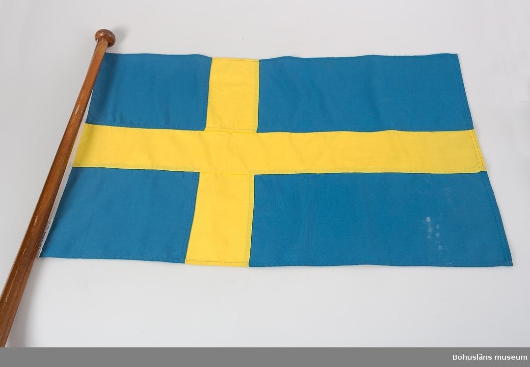 Svensk nationsflagga av syntettyg fästad på flaggstång av lackad mahogny. Flaggen sitter i båtens akter.