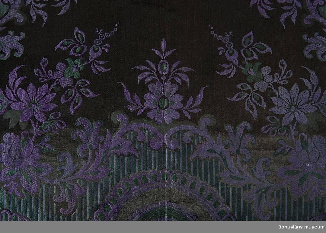 Svart/violett/grön sidenschal med frans. Jaquardvävt heltäckande blommönster. Handknuten frans, 11 cm lång. Handfållad. Rund röd stämpel i ena hörnet med texten SVENSK TILLVERKNING. Möjligen kan det vara av K. A. Almgrens tillverkning. Plagget har tilllhört Anna Maria Berndtsdotter (1848 - 1938) på Hallsbäck Uppegård. Hon var gift med hemmansägaren och styrmannen Karl Berndtsson (1846 - 1933). Familjen hade två barn, Hilma Lovisa Karlsdotter (1878 - 1965) och Karl Berndt Gardell (1883 - 1962).  I gåvan ingår ytterligare schalar av siden och bomull liksom ett handvävt lakan, se UM031735 - UM031739.