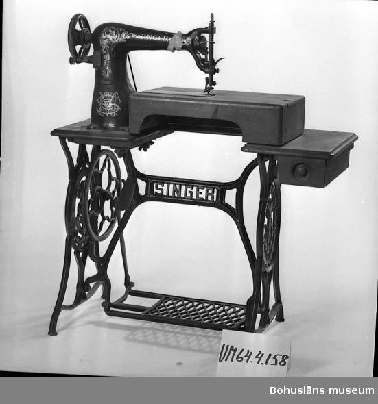 """471 Tillverkningstid 1910 CA 503 Kön MAN  Svartlackerad symaskin med gulddekor, med växtornamentik, på gjutjärnsunderrede. Underredet även det i svart och guld, på gavlarna firmamärke i en oval form: """"SINGER MANFG. CO, TRADE MARK"""" med nål, tråd och lagerbladsfestong.  Arbetsskiva i fanerat, enkelt profilerat trä. Vid undre delen av maskinen, brevid nålen är bordsskivan ursågad och förhöjd med 12,5 cm, För att komma åt att byta spole finns ett skjutlock.  På vänster sida finns en låda med knopphandtag, den innehåller bl.a. läderbitar, en sönderklippt handske, väsklås, skospännen, symaskinsspolar, en burk med nålar, en ask med nålar, ett set för att laga cykelslangar, knappar och lösa symaskinsdelar.  På högra undersidan av bordet sitter ett reglage som troligen styrs med knäet. Maskinen märkt dels med en mässingsplatta som är likadant utformad som de på underredsgavlarna, dels plattor med stansade nr: """"A212341"""" och """"18-3"""".  Trampdriven, drivrem saknas. Skivan är fläckig med bl.a. ringmärken. Tapetrester på armen,  Gjutjärnsdelarna är insmorda med något dinitrolliknade material.  Övriga uppgifter: Se UM64.04.001.  Inventerat 1996-08-13 CB  Ur punktnummerkatalogen 1958-1976: G. Arsenius, dödsbo Skomakariverkstad G. Arsenius, skomakeri U:a"""